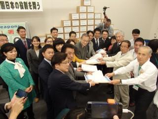 (写真)日本共産党の国会議員団に「核兵器全面禁止のアピール」署名を手渡す日本原水協の人たち=27日、衆院第1議員会館